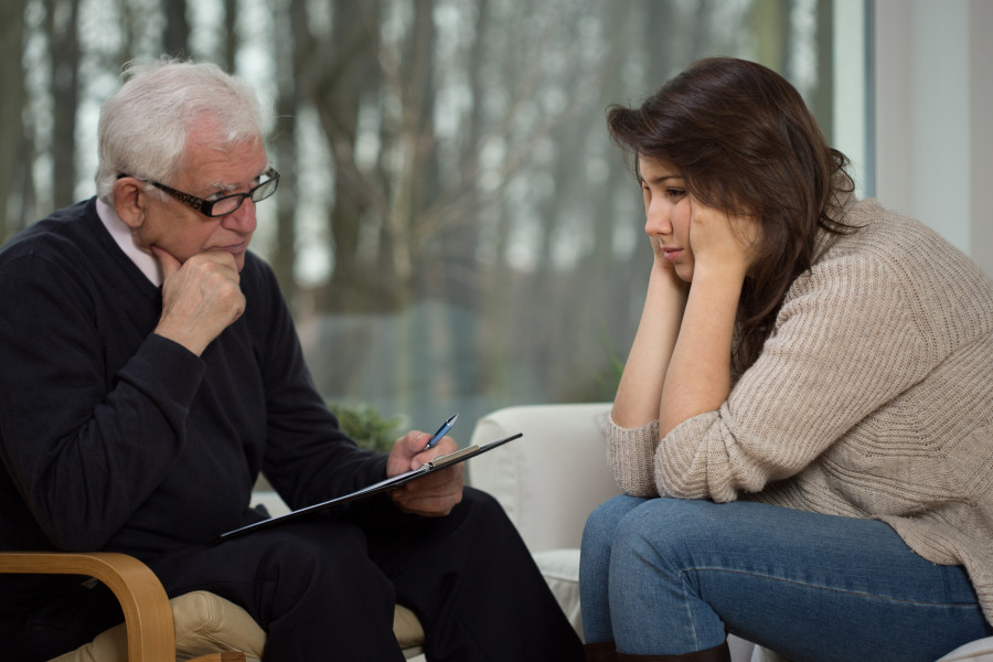 Older experienced psychologist diagnosing young troubled woman